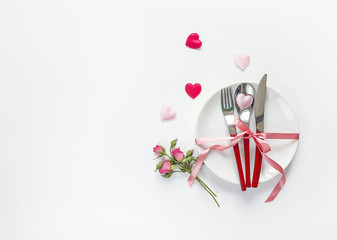 Romantic festive table setting with cutlery, roses and hearts on