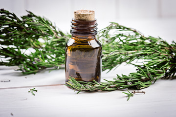 Rosemary essential oil on a  bottle with  fresh rosemary on wooden background, selective focus.