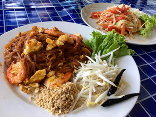 Background Thai food style. Noodles with shrimp and salad with papaya. Spicy meal Pad Thai style.
