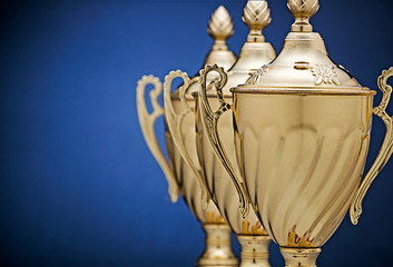 Row of three gold trophy cups on blue