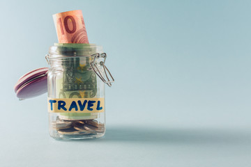 jar with money on blue background. copy space. holiday savings