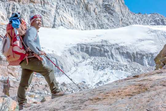 Nepalese Mountain Guide staying on top of high Rock