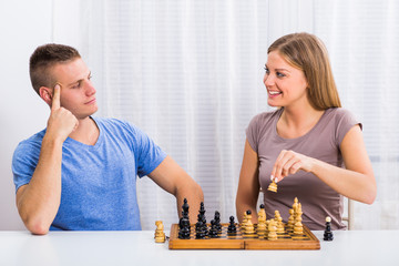 Happy couple enjoys playing chess.