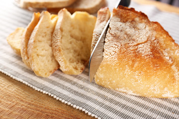 Slicing of fresh bread with knife on fabric closeup