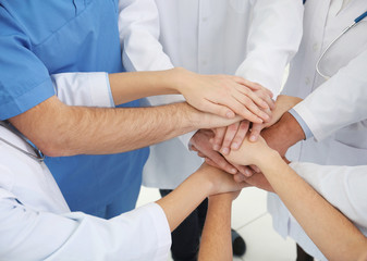 Team of doctors putting hands together, closeup