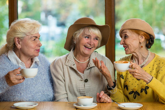 Elderly ladies in cafe smiling. Conversation of old women. Rumors and gossips.