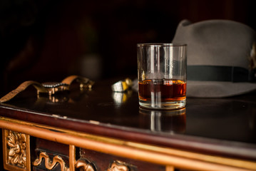 Glass of whiskey and men's watches on the wooden retro table