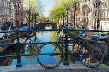 bicycle standing on the bridge next to canal in Amsterdam, Netherlands
