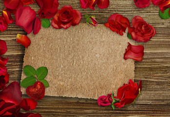 Red rose petals, red roses and red heart on wooden background. Place for text. Valentine's card