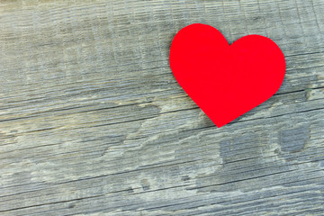 Red heart made of cardboard on the old wooden background