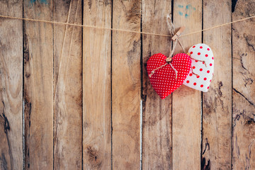 Two heart fabric hanging on clothesline and wood background with