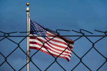 American flag and defocused fence, the United States confrontation and refugees