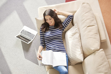 Enjoy relaxing at home. High angle shot of a happy young woman enjoy to reading a magazine while relaxing at home.