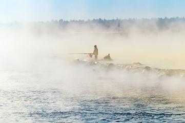 одинокий рыбак на туманном озере с удочкой, ранним утром