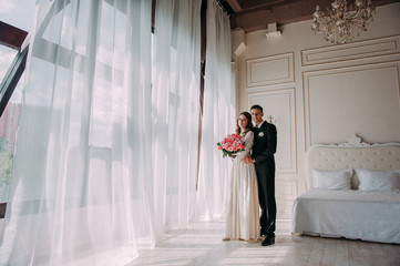 cute wedding couple in the interior of a classic white studio decorated. hey kiss and hug each other, holding hands looking at each other