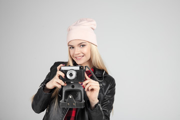 Portrait of pretty blond hair smileing young teenage hipster woman model with retro photo camera wearing a pink hat, black leather jacket. Fashion look.