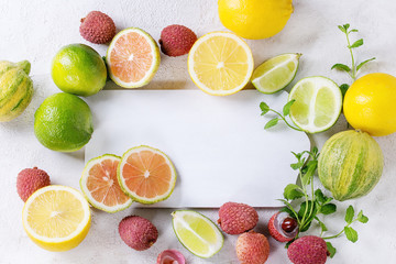 Variety of whole and sliced citrus fruits pink tiger lemon, lemon, lime, mint and lichee with empty cutting board over white concrete textured background. Top view, space for text, healthy eating