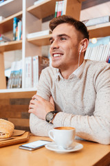 Young happy man listening music and drinking coffee.