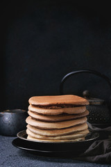 Stack of homemade american ombre chocolate pancakes served on black plate with jug of cream and teapot over black stone texture background.