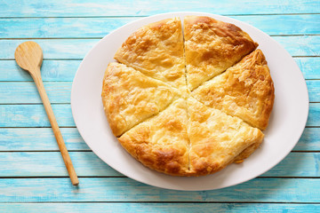 Greek cheese pie on a blue washed table