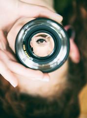 Ojo de una mujer enfocado desde un objetivo de fotografía