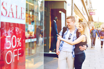 Young couple looking at shop's window in city with sale add