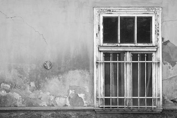 Old window with bars and curtains on an old wall in black and white tones