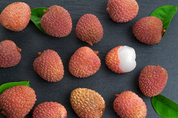 Fresh pile of lychees with leaves on black stone background