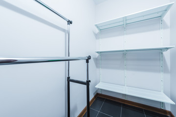 The interior of the new dressing room with hangers and shelves for clothes in white