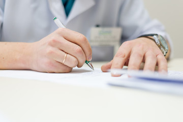 male doctor sitting table writing. hands