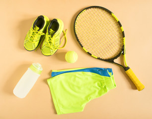 Sport, fitness, tennis, healthy lifestyle, sport stuff. Tennis racquet, lime trainers, tennis ball, lime athletic shorts, sports bottle. Flat lay, top view.