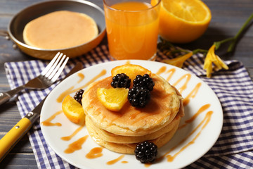 Stack of fresh pancakes with fruits on plate, closeup