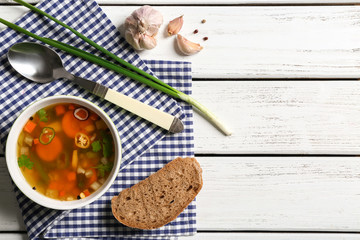 Soup with fresh vegetables and bread on napkin