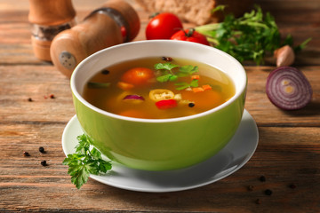 Bowl with fresh vegetable soup on wooden background