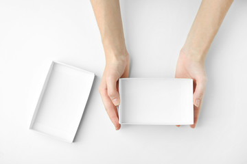Female hands with open box on white background