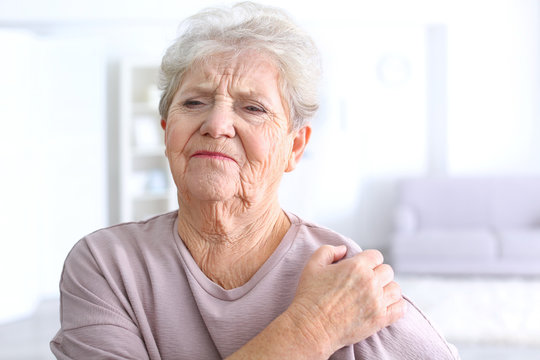 Elderly woman suffering from pain in shoulder at home