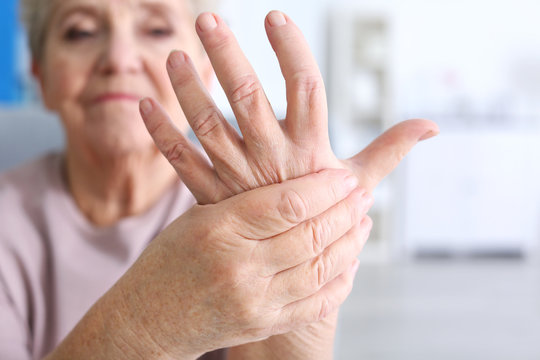 Elderly woman suffering from pain in hand, closeup