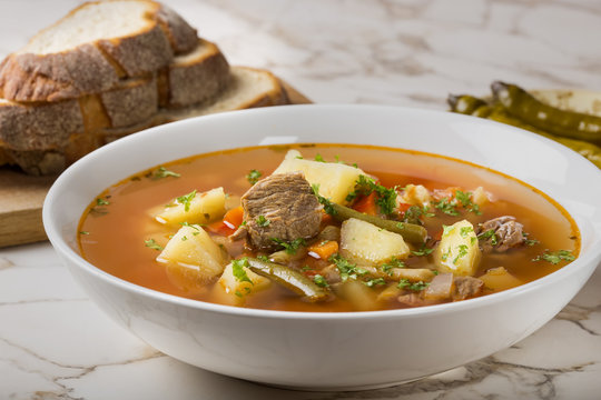 Bowl of vegetable beef soup with bread and hot chilli peppers in