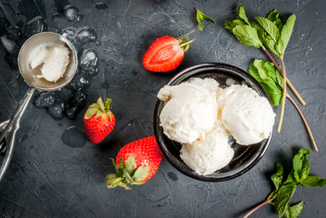 Vanilla ice cream in a classic ice-cream bowls with strawberries and mint, ice cream spoon on dark gray stone table