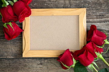 photo frame and red roses on wooden background.