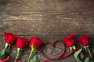 Red roses and heart shaped ribbon background.