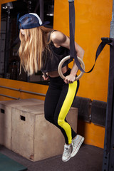 Fitness woman doing ring dips in the gym