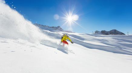Fototapete - Freerider snowboarder running downhill