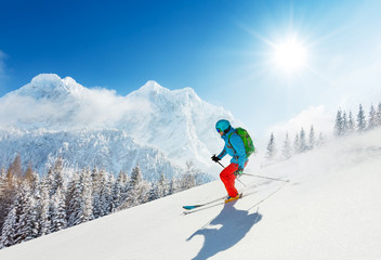 Fototapete - Free-ride skier in fresh powder snow running downhill