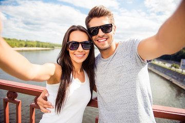 Cheerful happy man and woman having walk and making selfie