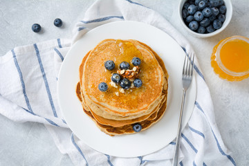 Stack of pancakes with blueberries, walnuts and honey served on white plate over gray background. Top view