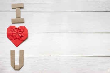 Red origami heart, craft paper folded letters I Love You (I, U) inscription on white painted rustic rural barn wood background.