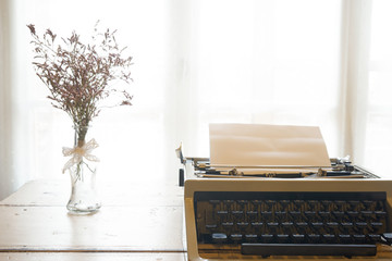 Vintage typewriter and dry flowers front a window