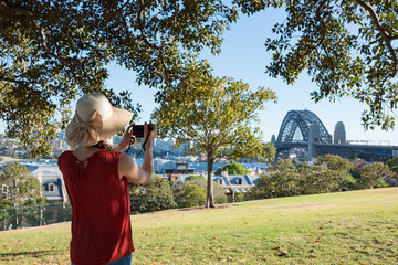 Woman in summer hat taking pictures of Sydney Harbour