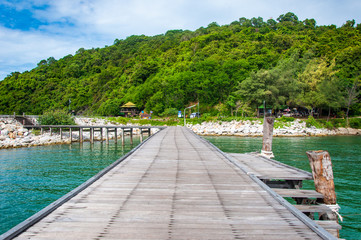 Beautiful Wooden Jetty  with Dramatic Sky and Green Island Backg